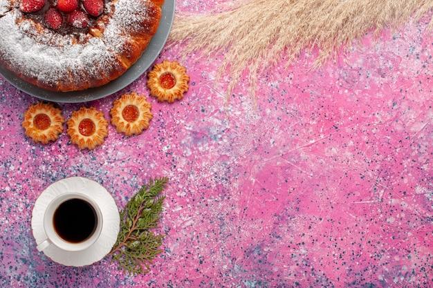 Bovenaanzicht heerlijke aardbeientaart suiker poedertaart met koekjes en kopje thee op lichtroze achtergrond cake zoete suiker koekjes taart
