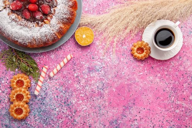 Bovenaanzicht heerlijke aardbeientaart suiker poedertaart met koekjes en kopje thee op roze bureau cake zoete suiker koekjes taart
