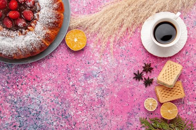 Bovenaanzicht heerlijke aardbeientaart suiker poedertaart met wafels en kopje thee op roze bureau cake zoete suiker koekjes taart