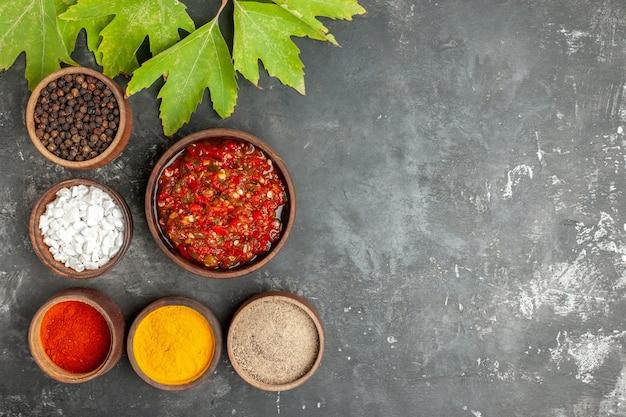 Bovenaanzicht heerlijke adjika in houten kom verschillende kruiden in kleine kommen op grijze achtergrond