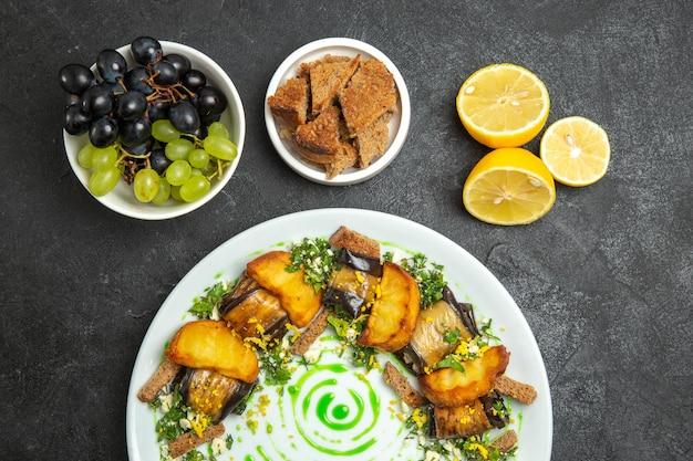 Bovenaanzicht heerlijke aubergine broodjes met gebakken aardappelen in plaat op de donkere achtergrond schotel maaltijd diner eten aardappel groente