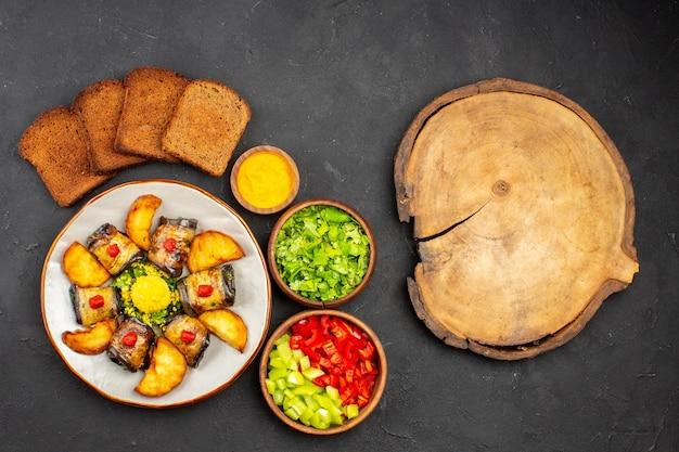 Bovenaanzicht heerlijke aubergine rolt gekookt gerecht met gebakken aardappelen en brood op de donkere achtergrond schotel koken voedsel aardappel bak bakken