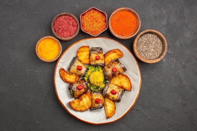 Bovenaanzicht heerlijke aubergine rolt gekookt gerecht met gebakken aardappelen en kruiderijen op donkere achtergrond schotel maaltijd diner eten koken aardappel