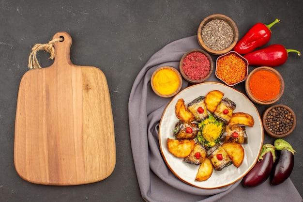 Bovenaanzicht heerlijke aubergine rolt gekookt gerecht met gebakken aardappelen en smaakmakers op de donkere achtergrond voedsel maaltijd gerecht aardappel koken