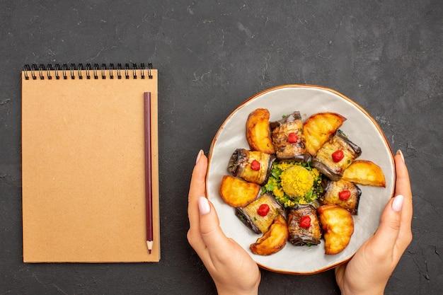 Bovenaanzicht heerlijke aubergine rolt gekookt gerecht met gebakken aardappelen op de donkere achtergrond aardappelschotel maaltijd diner eten koken