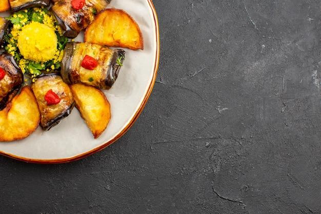 Bovenaanzicht heerlijke aubergine rolt gekookte schotel met gebakken aardappelen op donkere achtergrond maaltijdschotel koken voedsel bak aardappel