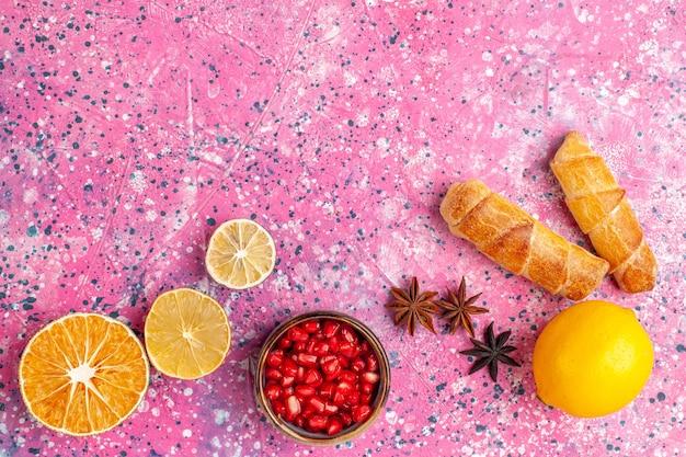 Bovenaanzicht heerlijke bagels met citroen op roze bureau