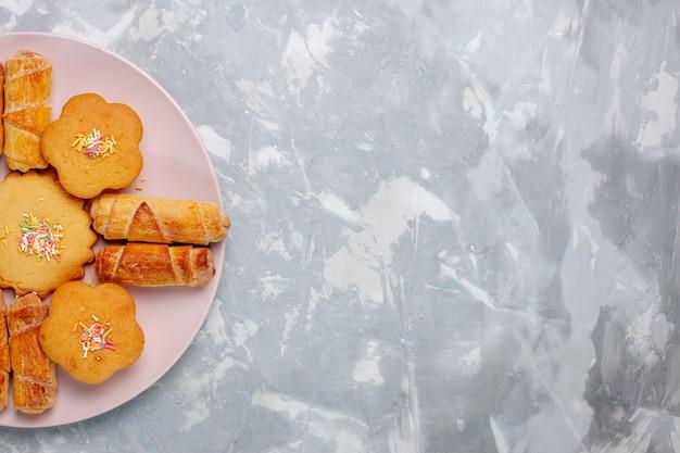 Bovenaanzicht heerlijke bagels met gebak in plaat op het witte bureau