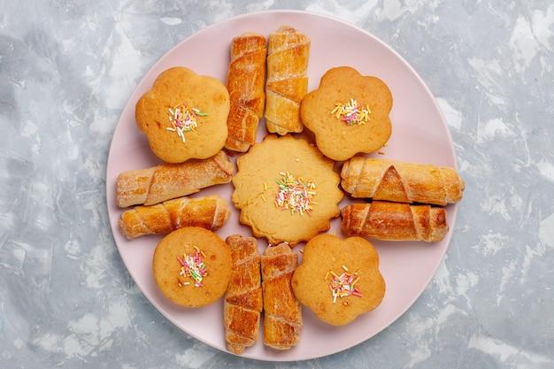 Bovenaanzicht heerlijke bagels met gebak in plaat op witte ondergrond