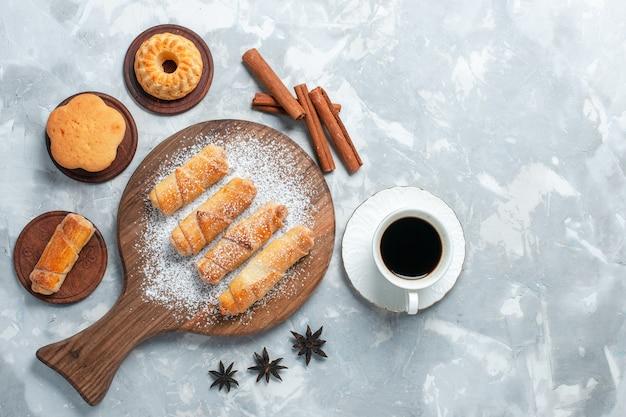Bovenaanzicht heerlijke bagels met kleine cakes, thee en koekjes op lichtwitte achtergrond.