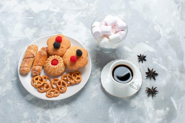 Bovenaanzicht heerlijke bagels met koekjescrackers en taarten met thee op licht wit bureau.