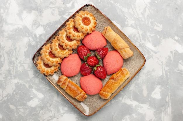 Bovenaanzicht heerlijke bagels met taarten, verse aardbeien en koekjes op wit bureau