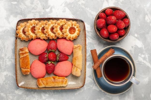Bovenaanzicht heerlijke bagels met taarten, verse aardbeien thee en koekjes op wit bureau