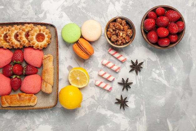 Bovenaanzicht heerlijke bagels met taarten, verse rode aardbeien en koekjes op wit bureau