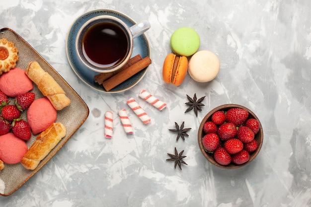 Bovenaanzicht heerlijke bagels met taarten, verse rode aardbeien macarons en koekjes op wit bureau