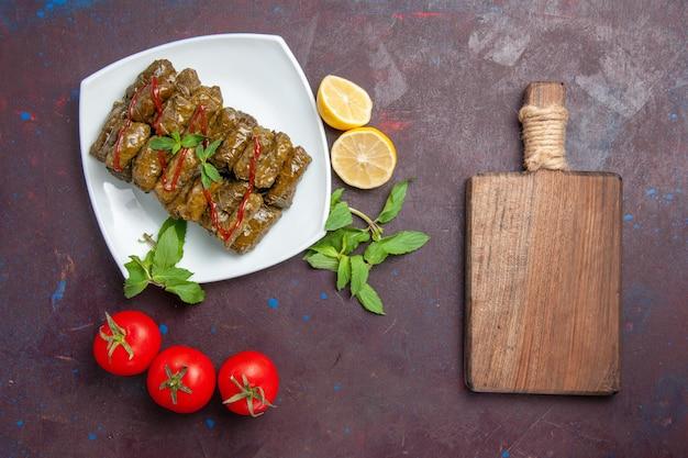 Bovenaanzicht heerlijke blad dolma gehaktschotel met citroen en tomaten op de donkere achtergrond schotel blad diner eten vlees