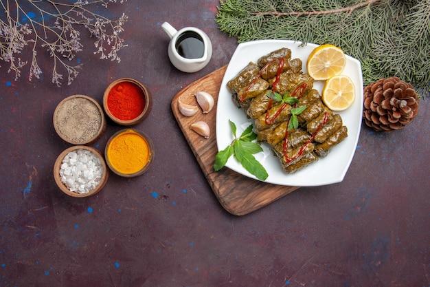 Bovenaanzicht heerlijke bladdolma met schijfjes citroen en kruiden op de donkere achtergrond vleesmaaltijd schotel blad diner eten