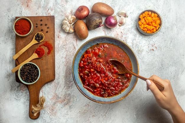 Bovenaanzicht heerlijke borsch oekraïense bietensoep met kruiden op witruimte on