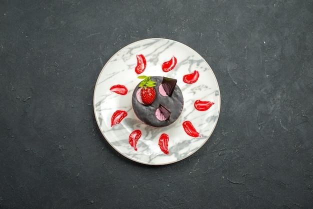 Bovenaanzicht heerlijke cake met aardbei en chocolade op ovale plaat op donkere achtergrond