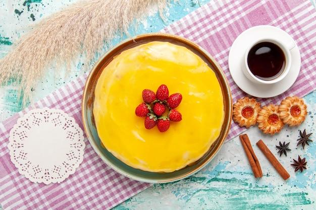 Bovenaanzicht heerlijke cake met gele stroop verse rode aardbeien en kopje thee op het blauwe bureau biscuit cake bakken zoete suikertaart thee