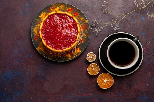 Bovenaanzicht heerlijke cake met rode room en kopje koffie op de donkere achtergrond biscuit cake suiker dessert taart zoete koekjes