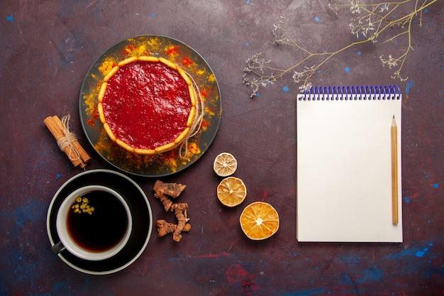 Bovenaanzicht heerlijke cake met rode room en kopje koffie op donkere achtergrond biscuit cake suiker dessert taart zoete cookie