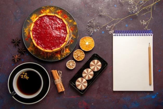 Bovenaanzicht heerlijke cake met rode roomkoekjes en kopje koffie op donkere bureau koektaart suiker dessert taart zoete koekjes
