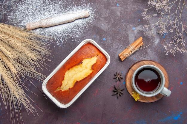 Bovenaanzicht heerlijke cake perfecte snoepjes voor kopje thee op donkere achtergrond thee zoete taart cake koekjesdeeg suiker