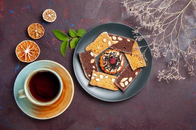 Bovenaanzicht heerlijke cake plakjes met kleine koekje en kopje thee op de donkere achtergrond biscuit cookie dessert cake thee zoet