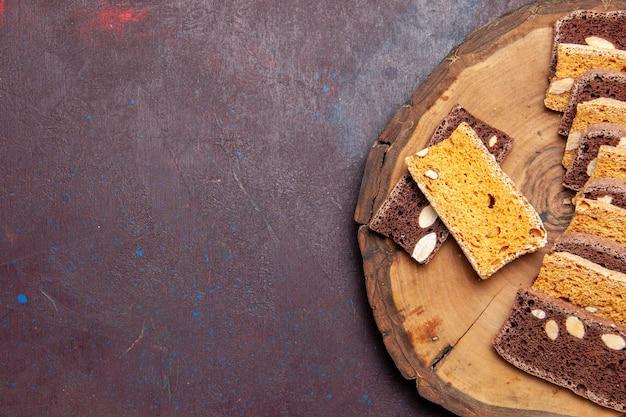 Bovenaanzicht heerlijke cake plakjes met noten op de donkere achtergrond thee suiker koekjes biscuit cake zoete taart