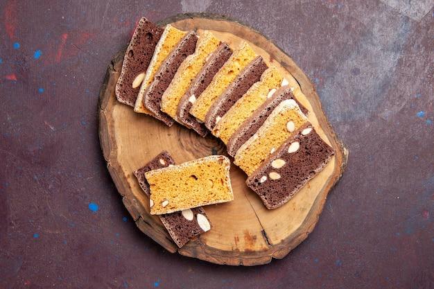 Bovenaanzicht heerlijke cake plakjes met noten op donkere achtergrond thee cake suiker koekjes taart biscuit zoet