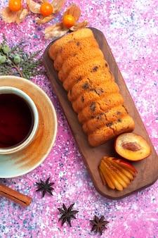 Bovenaanzicht heerlijke cake zoet en lekker met pruimen kaneel en kopje thee op de roze achtergrond.