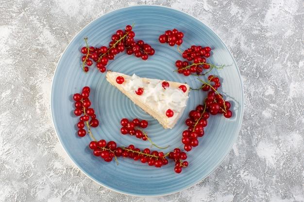 Bovenaanzicht heerlijke cakeplak binnen blauwe ronde plaat met room en rode veenbessen op de grijze achtergrond koekjescake thee zoete suiker