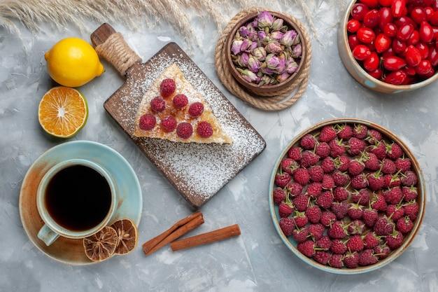 Bovenaanzicht heerlijke cakeplak met kopje thee frambozen kornoeljes op het licht bureau cake koekje zoete suiker bakken