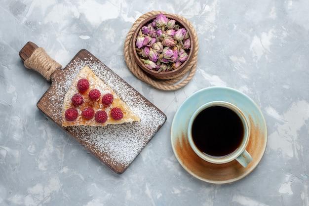 Bovenaanzicht heerlijke cakeplak met kopje thee op het lichtbureau cakekoekje zoete suiker bakken