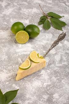 Bovenaanzicht heerlijke cakeplak met stukjes limoen en verse limoenen op de lichte achtergrond cake zoete suiker bakken deeg