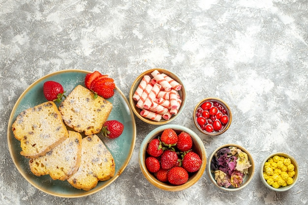 Bovenaanzicht heerlijke cakeplakken met fruit en snoep op lichte ondergrond cake zoete taart