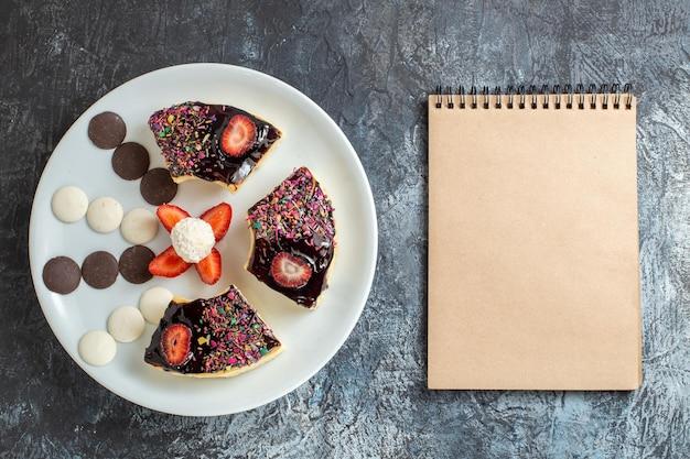 Bovenaanzicht heerlijke cakeplakken met kleine koekjes op donker bureau