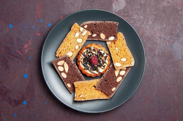 Bovenaanzicht heerlijke cakeplakken met noot en klein koekje op donkere achtergrondkoekje, zoete dessertcake