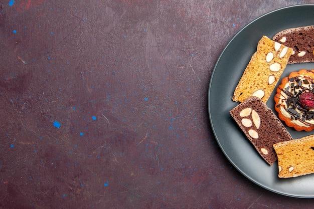 Bovenaanzicht heerlijke cakeplakken met noten en klein koekje op een donkere achtergrond, zoete koekjeskoekjesdessertcake