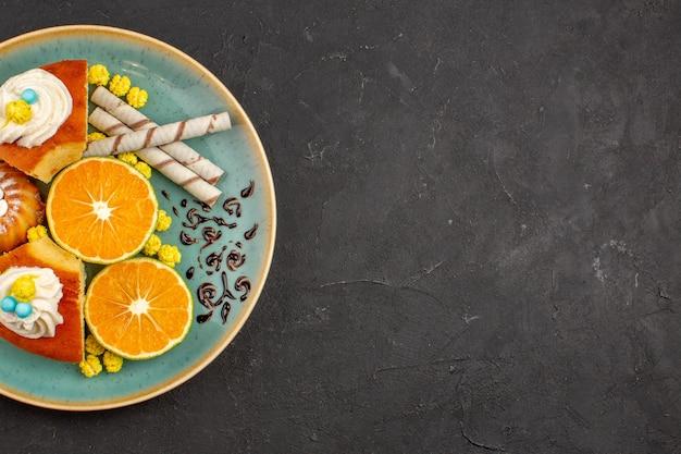 Bovenaanzicht heerlijke cakeplakken met pijpkoekjes en gesneden mandarijnen op donkere achtergrond, fruit, citruscake, taartkoekjes, zoete thee