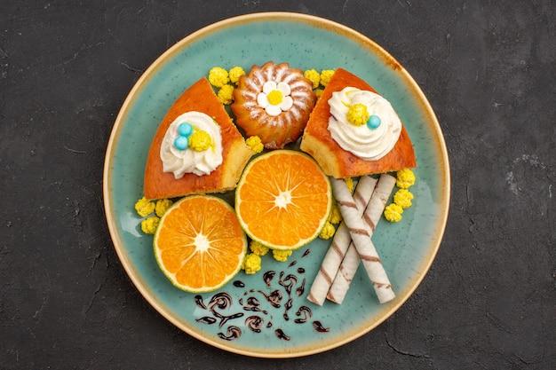 Bovenaanzicht heerlijke cakeplakken met pijpkoekjes en gesneden mandarijnen op een donkere achtergrond, fruit, citruscake, taartkoekje, zoete thee