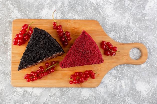 Bovenaanzicht heerlijke cakeplakken met roomchocolade en fruit op het houten bureau zoete zoete cake