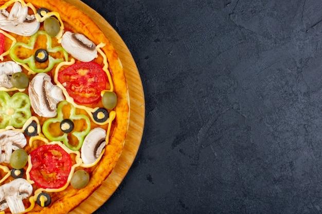 Bovenaanzicht heerlijke champignonpizza met rode tomaten, paprika, olijven en champignons, allemaal binnen gesneden op de donkere bureau