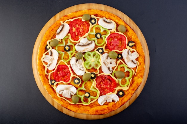 Bovenaanzicht heerlijke champignonpizza met rode tomaten paprika olijven en champignons allemaal binnen gesneden op het donkere bureau eten maaltijd pizza italiaans