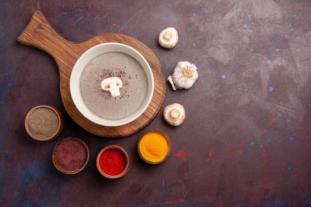 Bovenaanzicht heerlijke champignonsoep met kruiden op donkere ruimte