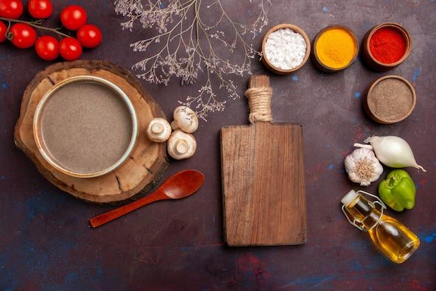 Bovenaanzicht heerlijke champignonsoep met kruiden op donkere ruimte Gratis Foto