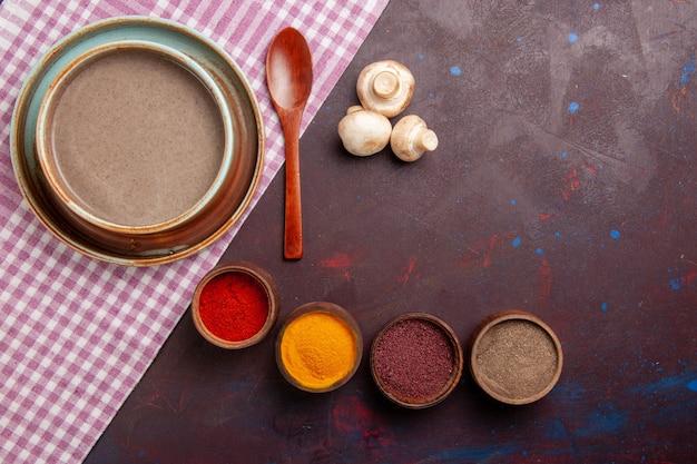 Bovenaanzicht heerlijke champignonsoep met verschillende kruiden op donkere ruimte