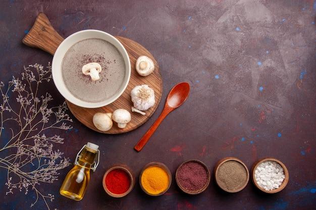 Bovenaanzicht heerlijke champignonsoep met verse champignons en kruiden op donker bureau