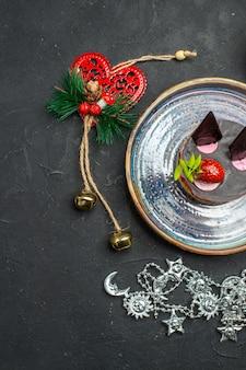 Bovenaanzicht heerlijke cheesecake met aardbei en chocolade op ovale zilveren plaat xmas hangers op donkere geïsoleerde achtergrond